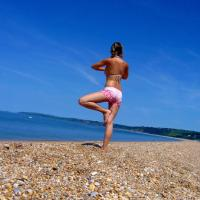 Girl Doing Yoga By The Beach