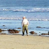 Man Walking Alone On The Beach
