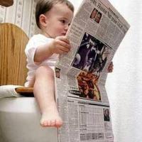 Toddler Reading Paper on Toilet